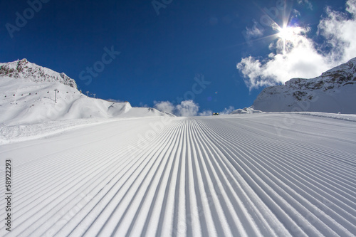 Fresh snow groomer tracks on a ski piste Fototapet