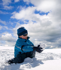 Fototapeta na wymiar Little boy having fun in the snow
