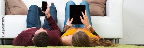 Photo paar spielt am handy und tablet