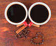 Red cups of strong coffee and coffee beans on wooden background
