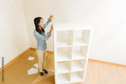 Fotografie, Tablou  Asian woman assemble a white bookshelf