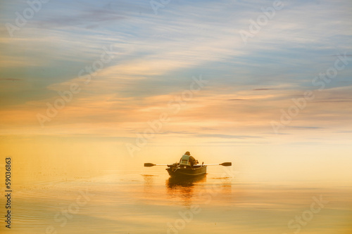 Photo Lonely man boating in the dawn