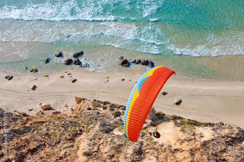 Photo sur Toile Aerien Paraglider soaring over the seashore
