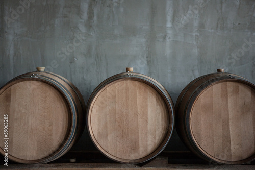 Wine barrels stacked in the cellar of the winery Fototapeta
