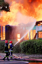 Firemen In Action On Burning Ruins Of Building
