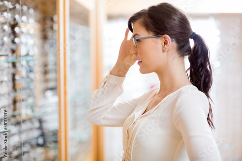 Deurstickers Ontspanning Woman Trying New Glasses At Optician Store
