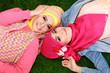 Leinwandbild Motiv Close up of two beautiful happy muslim woman lying on grass
