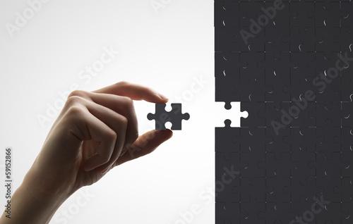 Fotografia  hand puts puzzle