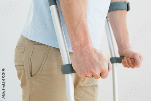 Fotografia Close-up mid section of a man with crutches