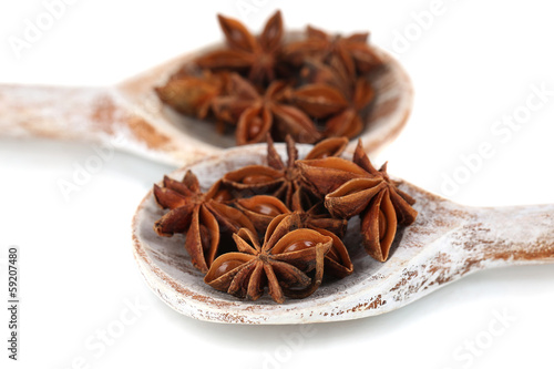 Tuinposter Kruiden 2 Star anise in wooden spoons, isolated on white