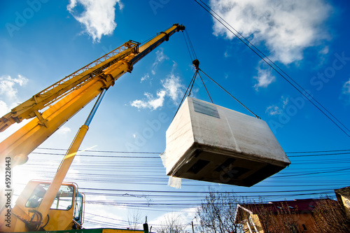 Photo  Industrial Crane operating and lifting an electric generator