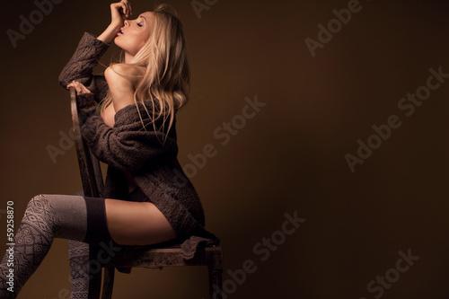 Fototapeta Beautiful, sensual blonde woman wearing long brown sweater, sitt obraz