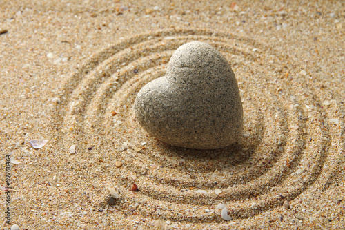 Foto op Aluminium Stenen in het Zand Grey zen stone in shape of heart, on sand background