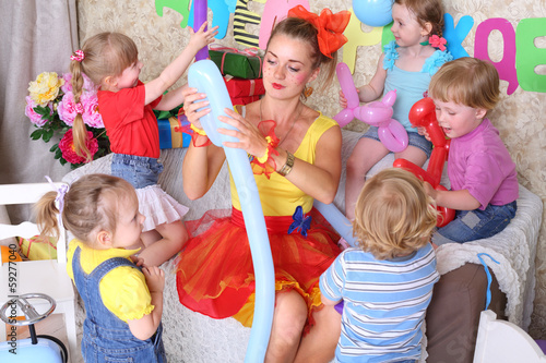 Fotografía  Five happy kids and facilitator make dogs of long balloons