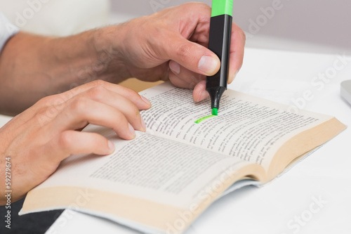 Fotografie, Obraz  Hands highlighting text in book on the table