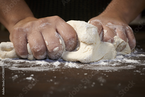 Fotografie, Obraz  woman's hands kneading dough on wooden table