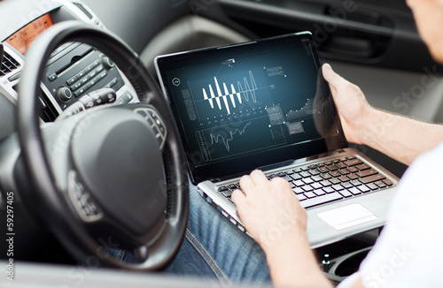 Fotografía  man using laptop computer in car