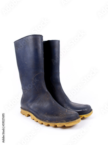 Fotografía  Pair of dark blue dirty rubber boots over a white background