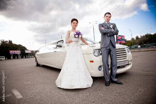 Young just married couple standing against long white limousine Poster