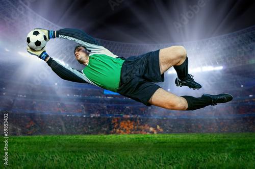 Staande foto Voetbal Football goalkeeper in action on field of stadium