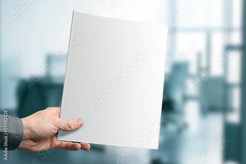 Photographie  Main tenant un magazine vide avec espace copie au bureau