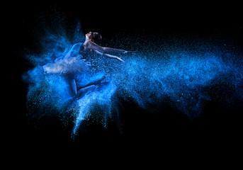 Mlada lijepa plesačica koja skače u oblak plavog praha