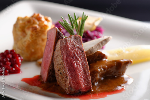 Venison meat steak with red cabbage, cranberries, herbs