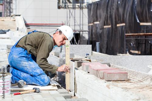Fotografia, Obraz  Worker with level examining marble tiles installation
