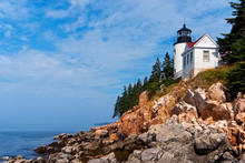 Bass Harbor Lighthouse Sits Above Jagged Rocky Cliffs In Acadia National Park During Low Tide In Maine. It Is A Favorite Summertime New England Tourist Attraction.