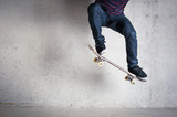 Skateboarder doing a skateboard trick - ollie - against concrete