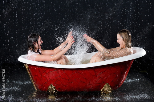 Photographie Two wet girls have fun and splashing water in bathtub