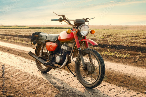Classic old motorcycle on a dirt road. Canvas Print