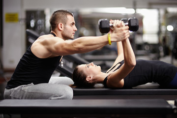 Fototapeta Personal trainer helping woman at gym