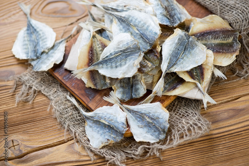 Fotografija Dried scad on a rustic wooden table, high angle view