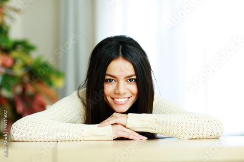 Fotografía  Cheerful young smiling woman leaning on the table at home