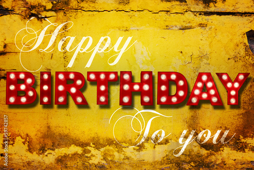 Glowing birthday greetings over distressed yellow paint