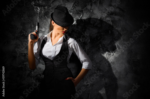 Obraz na plátně  Dangerous and beautiful criminal girl with gun