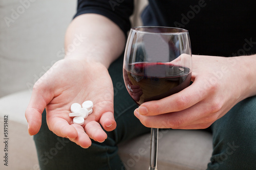 Woman taking painkillers and alcohol