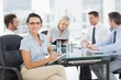 Businesswoman holding clipboard with colleagues discussing in of
