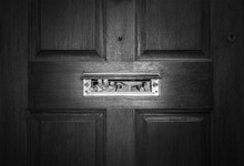 Man Peeping Through Letterbox. Black And White