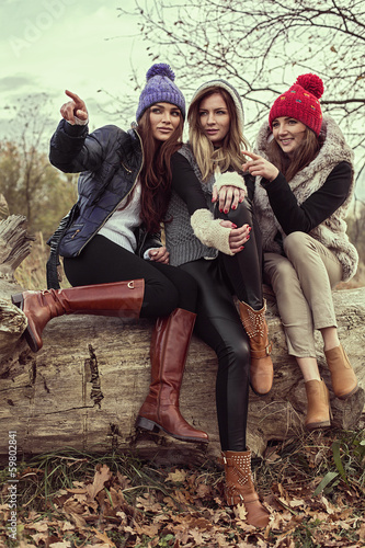 Happy tree girls wearing a woolly hats and showing something Wall mural