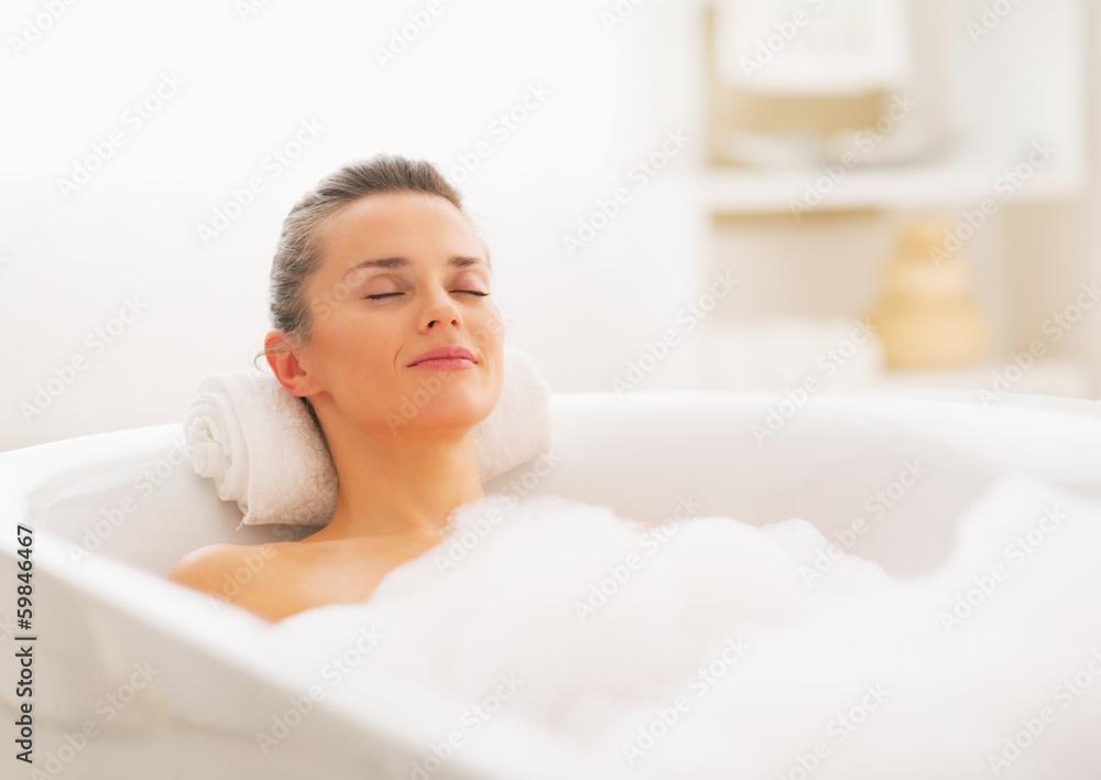 Fototapeta Happy young woman relaxing in bathtub