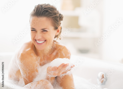Portrait of happy young woman playing with foam in bathtub Fototapete