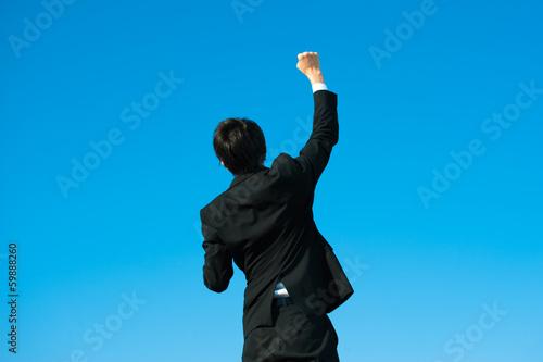 Fotografía  やる気を出す男性ビジネスマンの後ろ姿と青空