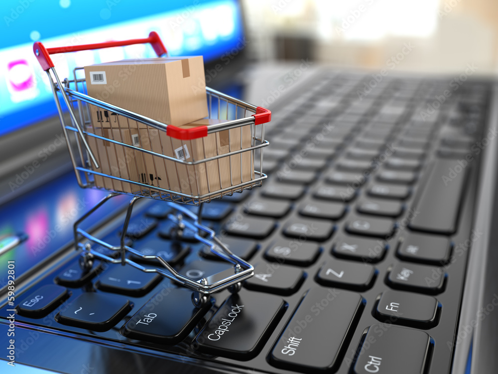Fototapeta E-commerce. Shopping cart with cardboard boxes on laptop.