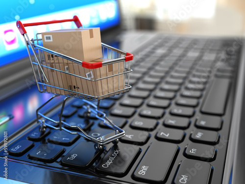 Foto E-commerce. Shopping cart with cardboard boxes on laptop.