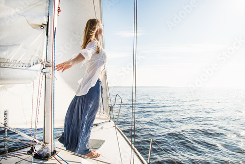 woman staying on sailboat Wallpaper Mural
