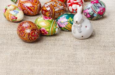 Easter eggs and ceramic rabbit on jute background
