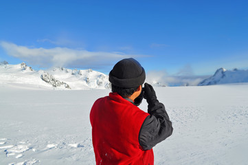 Fototapeta na wymiar Photographer shooting at top of ice mountain