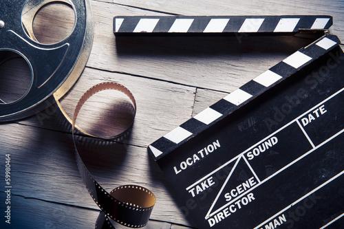 Photo  movie slate and film reel on wood